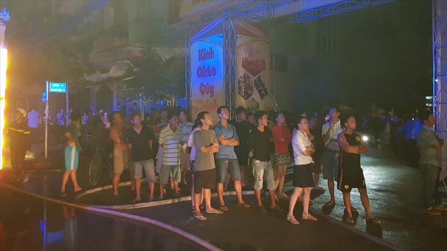 Hàng chục khách hát tháo chạy ra ngoài đang theo dõi lực lượng chữa cháy đưa các nạn nhân bị kẹt ra khỏi tòa nhà. Ảnh: Trường Sơn