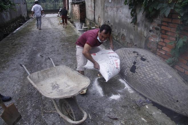 Hà Nội: 10 ngày sau lũ, người dân Tân Tiến rắc vôi bột trắng đường phòng bệnh dịch - Ảnh 8.