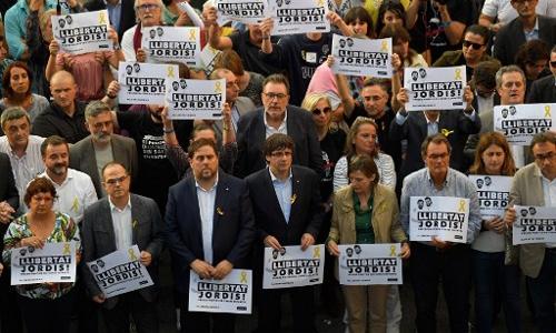 Ông Carles Puigdemont cùng các quan chức của vùng Catalonia và người dân biểu tình ở Barcelonia ngày 21/10 đòi Madrid phóng thích hai quan chức của vùng đang bị bắt giữ vì cáo buộc xúi giục nổi loạn. Ảnh: AFP.